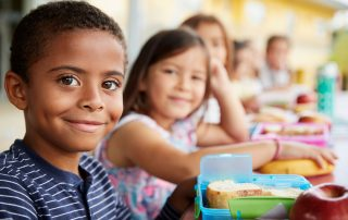 Smiling children eating lunch together, a topic for our charter school blog.