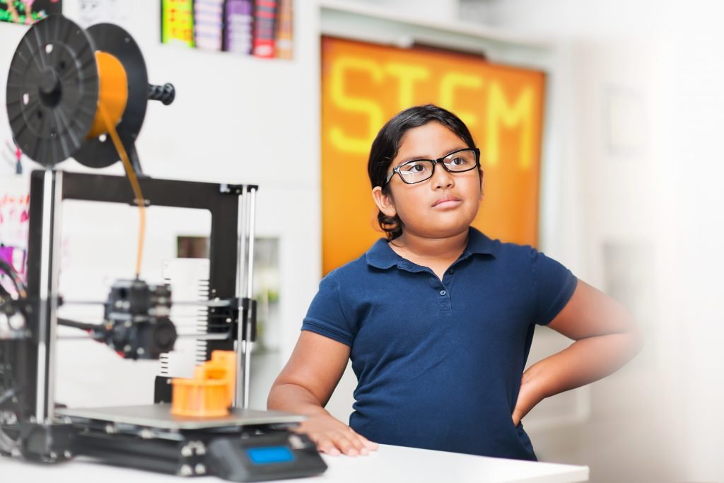 Young girl wearing glasses in a stem class, wondering what exactly is a charter school?