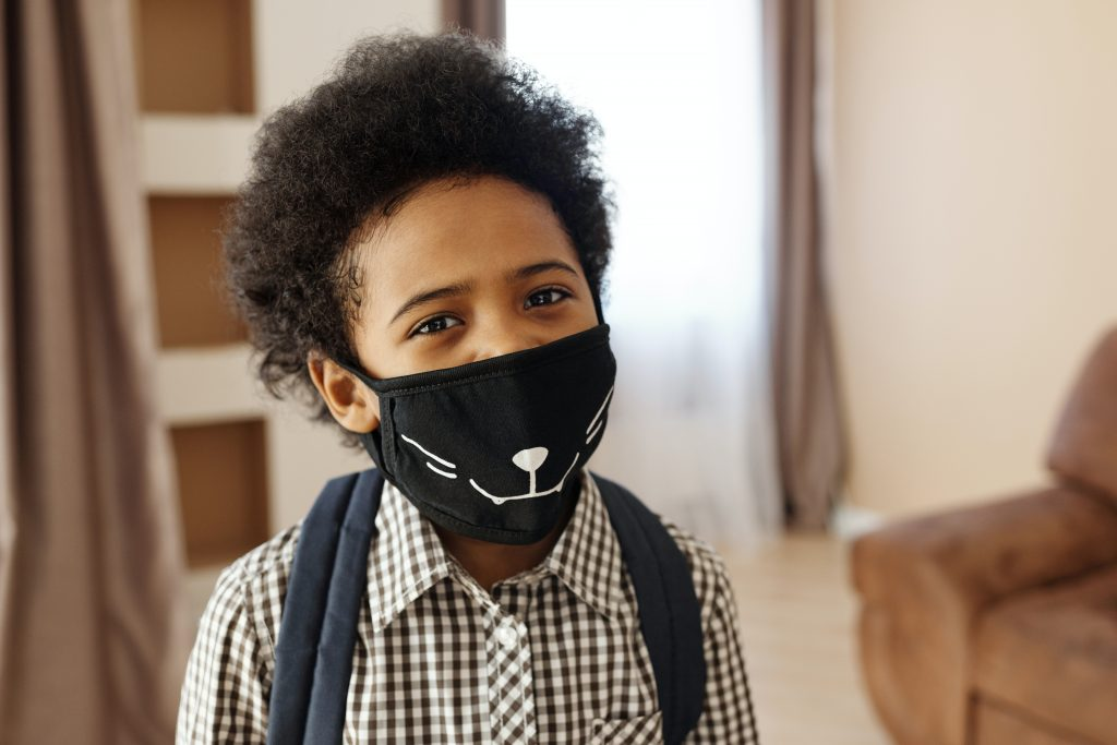 Young boy wearing a mask to protect against coronavirus and emerging Multisystem Inflammatory Syndrome in Children