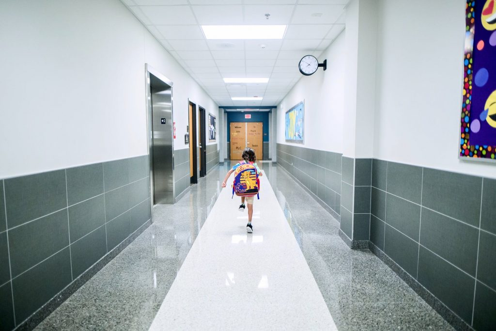 girl running down school hallway
